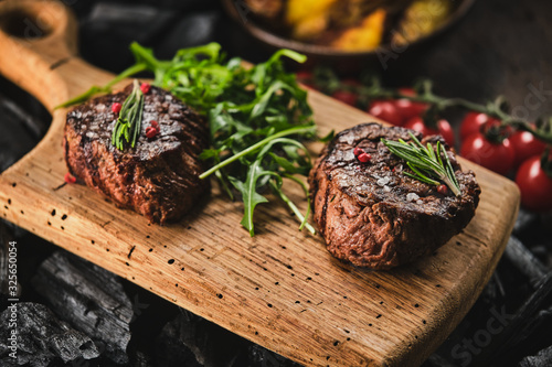 Fotografering Grilled fillet steaks on wooden cutting board