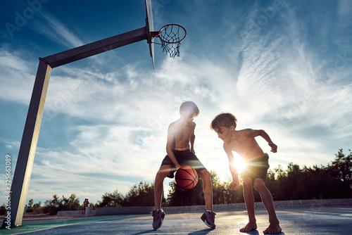 Zwei coole jungs spielen Basketball beim Sonnenuntergang am Meer Fototapet