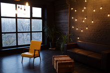 Modern Interior In A Dark Color With A Leather Sofa And Large Window. Loft Style Living Room