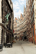 canvas print picture - Vertical view of narrow old traditional flemish street in centre of Antwerp, Belgium in cloudy day. Antwerpen popular famous travel tourism destination. Buildings and landmarks in Benelux