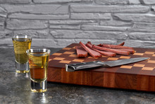 Two Whiskies In Small Glasses, A Kitchen Knife, And Sliced Dried Meat With Spices On A Cutting Board Against A Wall Of Rough, Pale Stone.