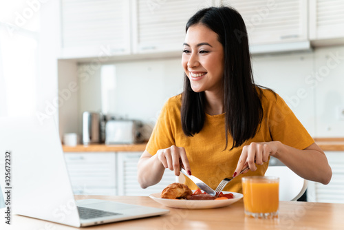 Photo Cheerful young woman using laptop computer have a dinner.