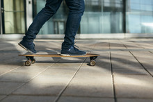 Man Skateboarding In City With One Foot Placed On Board And Pushing Off With The Other. Riding On Longboard On Paving Stone. Selective Focus On Skateboard. Concept Of Leisure Activity And Urban.