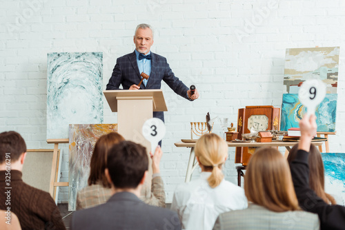 selective focus of auctioneer holding gavel and microphone and looking at buyers Canvas Print