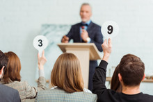 Back View Of Buyers Showing Auction Paddles With Numbers Nine And Three To Auctioneer During Auction