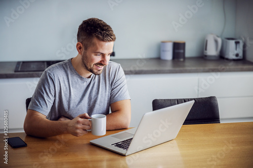 Obraz Young smiling man dressed casual sitting at dining table, holding mug with morning coffee and looking at laptop. He is visiting sites for online dating. - fototapety do salonu