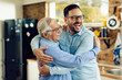 Cheerful mid adult man and his senior father embracing in the kitchen.
