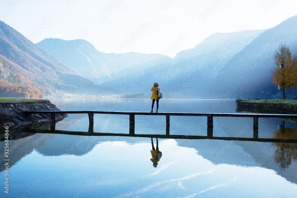 tourist girl in a hat and with a backpack stands on a wooden bridge