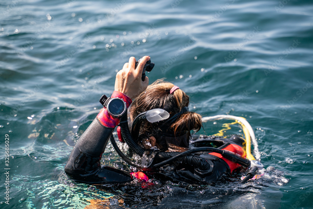 Fototapeta An Asian scuba diving girl with back wet suit waring dive computer at wrist