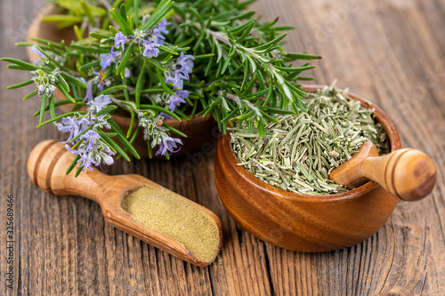 Fototapeta A wooden bowl with blooming and fresh rosemary twigs, a wooden bowl with whole dried rosmary and a spice shovel with ground rosemary on a rustic wooden background obraz