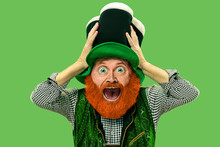Astonished, Shocked. Excited Leprechaun In Green Suit With Red Beard On Green Background. Funny Portrait Of Man Ready For Sales. Saint Patrick Day, Human Emotions, Celebration, Traditional Holidays.