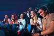 Leinwandbild Motiv Group of cheerful people laughing while watching movie in cinema.
