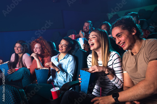Stampa su Tela Group of cheerful people laughing while watching movie in cinema.