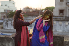 Two Beautiful And Young Indian Women Are Interacting With Each Other While Playing Holi On The Rooftop. Indian Lifestyle And Culture