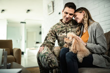 Happy Military Couple With Dog Sitting Embraced At Home.