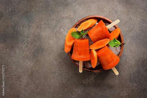 Homemade carrot popsicles with crushed ice and mint leaves in a bowl on a dark rustic background Fototapete