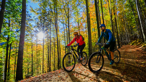 obraz PCV Cycling woman and men riding on bikes at sunset mountains forest landscape. Couple cycling MTB enduro flow trail track. Outdoor sport activity.