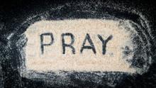 Flat Lay Of PRAY Text Written On White Sand