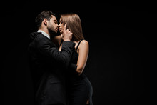 Side View Of Handsome Man Touching Face Of Attractive Woman In Dress Isolated On Black
