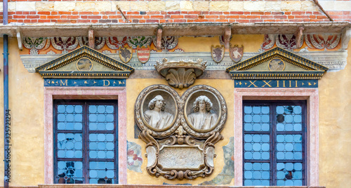 Facade of old building. Blue window. Bas-relief board with heads. Wallpaper Mural