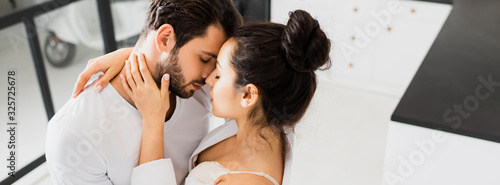 Fotografie, Tablou Panoramic shot of girl in bra and shirt kissing boyfriend at home