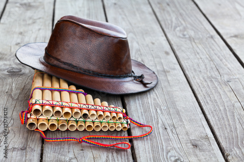 Fotografia, Obraz Multiple pipes pan flute and leather cowboy brown hat lying on square-edged floo