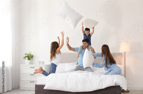 Papel de parede Happy family having pillow fight in bedroom
