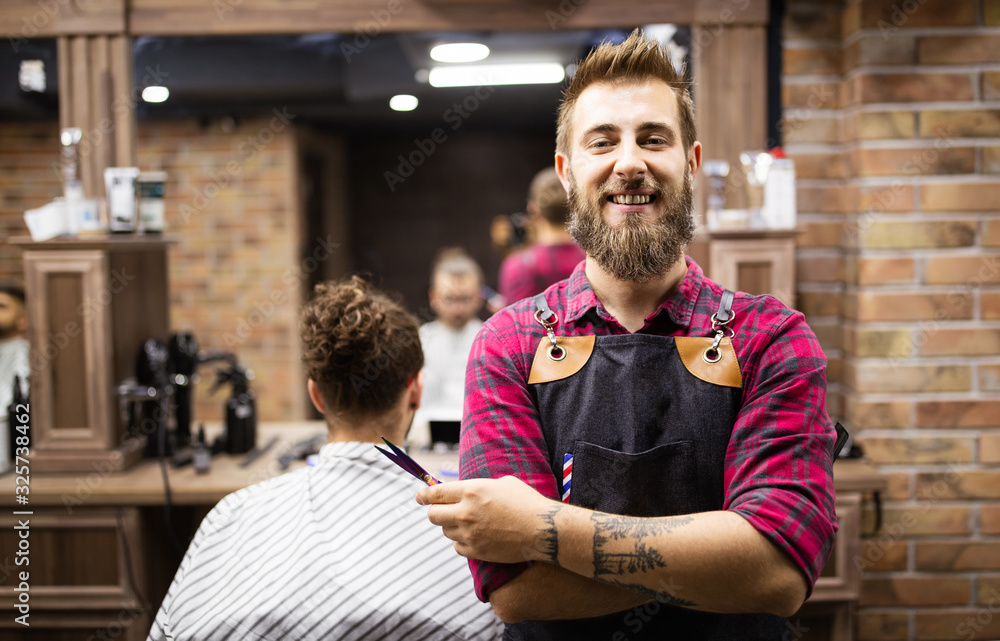 Fototapeta Portrait of happy young barber with client at barbershop and smiling.