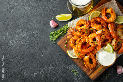 Photo Grilled shrimps or prawns served with lime, garlic and white sauce on a dark concrete background