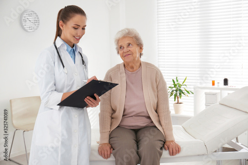 Obraz na płótnie Doctor examining senior patient in modern office