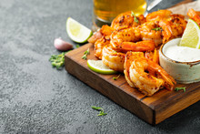 Grilled Shrimps Or Prawns Served With Lime, Garlic And White Sauce On A Dark Concrete Background. Seafood. With Copy Space
