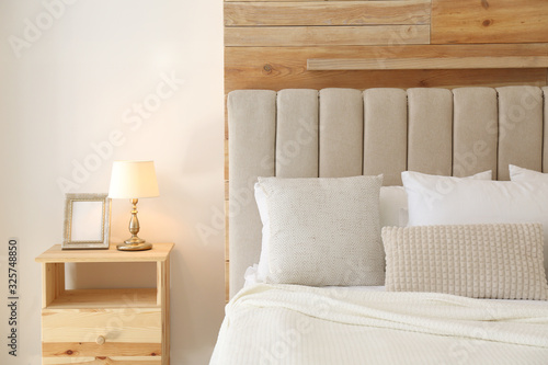 Comfortable bed with pillows in modern room interior Canvas Print