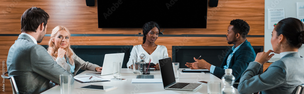 Fototapeta panoramic shot of young multicultural businesspeople talking while sitting in conference hall