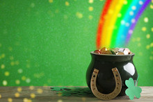 Pot With Gold Coins, Horseshoe And Clover Leaves On Wooden Table Against Green Background, Space For Text. St. Patrick's Day Celebration