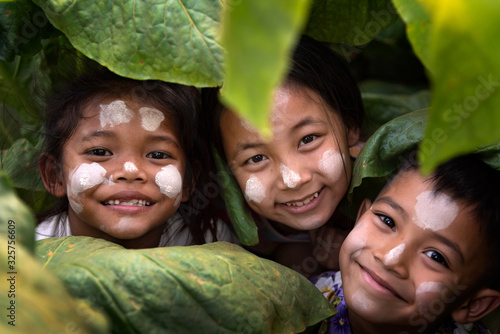 Tela Three children, a happy gym in Burma, smiling, local children in tobacco fields