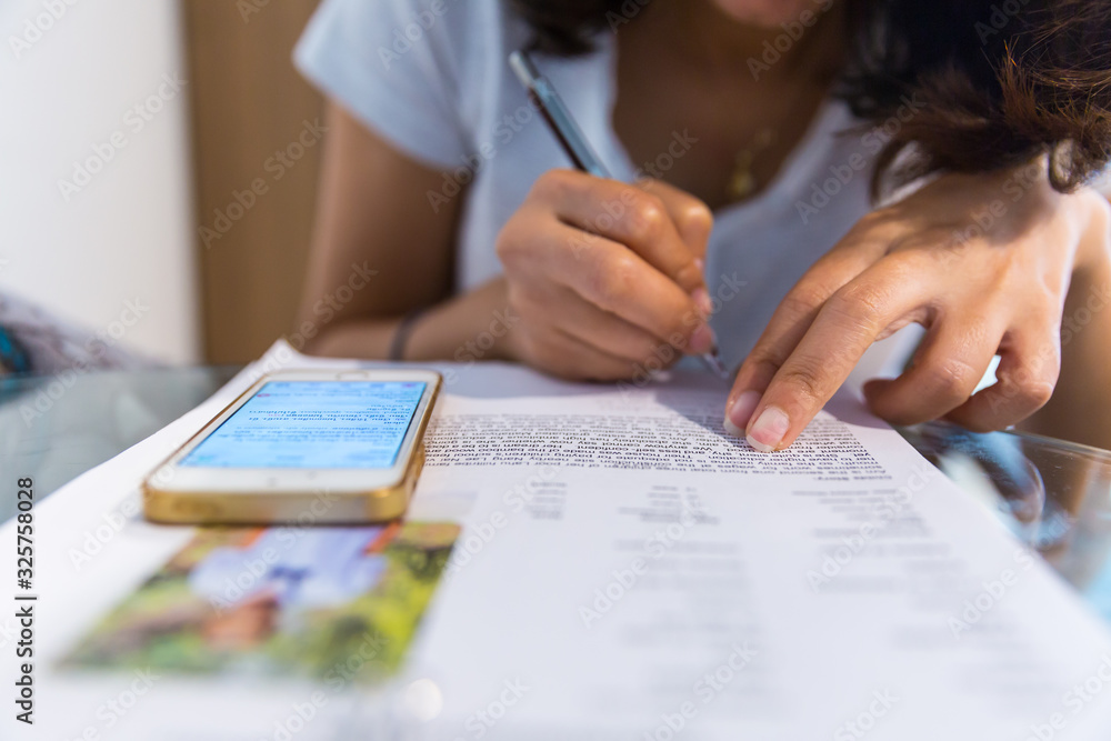 Young woman writing something in her note pad - obrazy, fototapety, plakaty