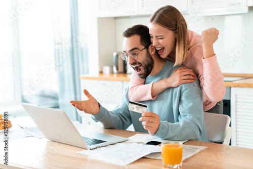 Portrait of young excited couple hugging while working with laptop