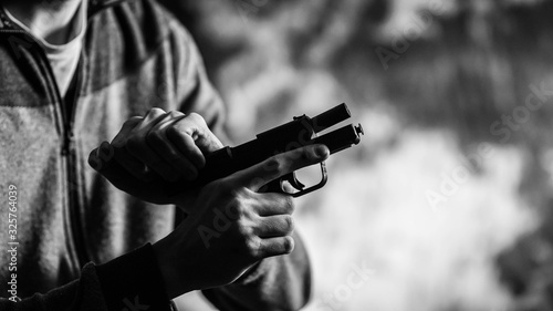 Photo Man cocking a small 9mm pistol