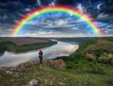 Fototapeta Tęcza - rainbow over the river. tourist on the rock. spring landscape