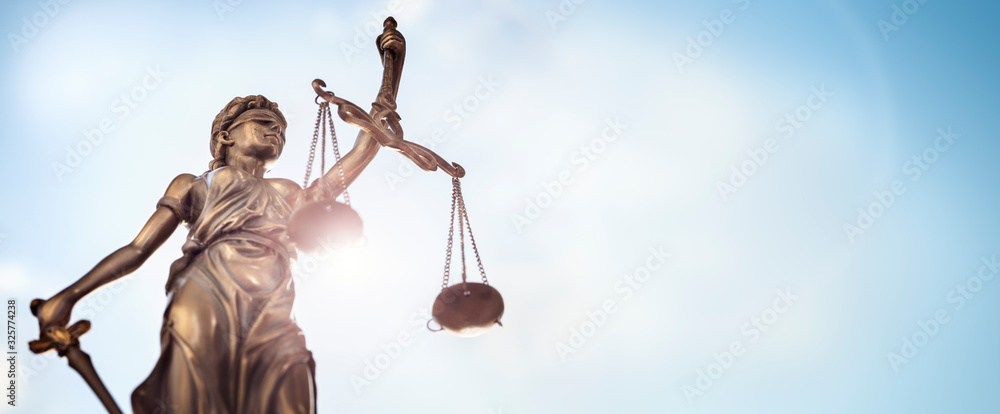 Fototapeta Legal law concept statue of Lady Justice with scales of justice sky background