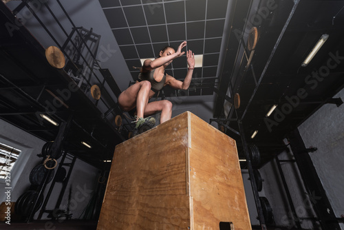 Obraz na plátne Young strong sweaty fit muscular girl with big muscles doing box jump hardcore c