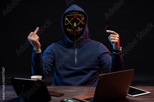 Fototapety, obrazy: dangerous anonymous hacker man in scary mask sit at table with laptop, aggressive hacker in the hood of pullover show middle finger at camera isolated over dark space