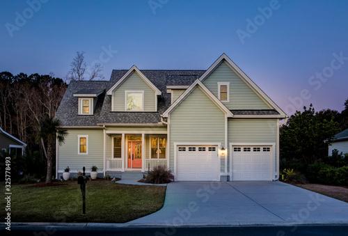Front elevation of beautiful home lit up at twilight. Fototapeta