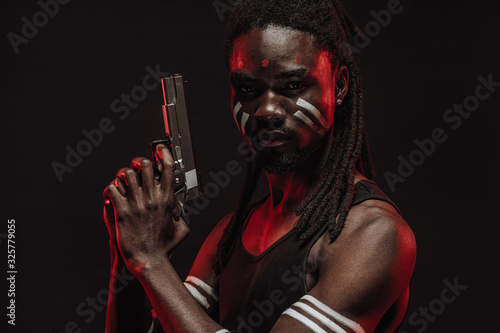 young serious african man in black shirt isolated over black background, dangerous man hold gun in hands ready to kill the enemy, red neon rays falling on his face Canvas Print