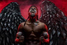 Dark Naked Angel Screaming From Hopelessness And Pain. Black Angel With Strong Muscles Want To Be Among Mortals But Is Impossible. Angel In The Fire Or In The Hell, Smoky Red Background