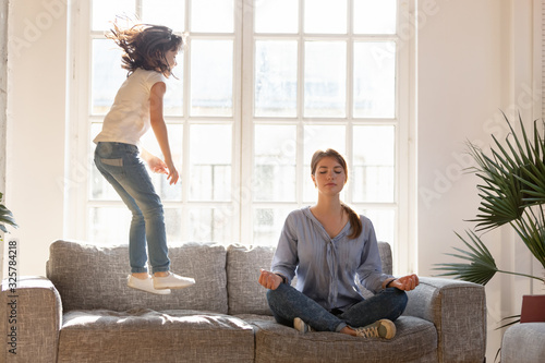 Obraz Mom meditating on couch ignore kid jumping near - fototapety do salonu