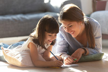 Happy Mom And Kid Have Fun Drawing In Album Together