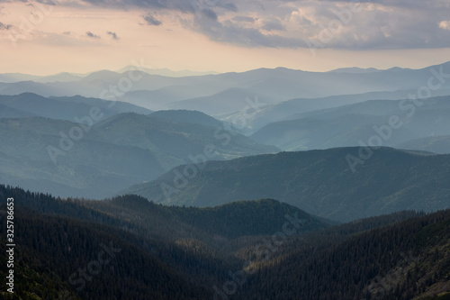 Misty spring mountain hills landscape. Layers of green mountains and hills in the haze during sunset. Concept nature background. #325786653