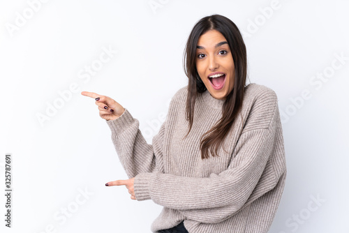 Fototapeta Young brunette woman over isolated white background surprised and pointing side obraz