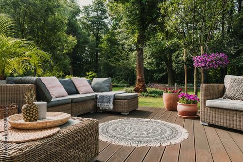 Classy furniture on wooden terrace in green beautiful garden Fototapete